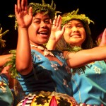 Smiling children dance in colourful national costume